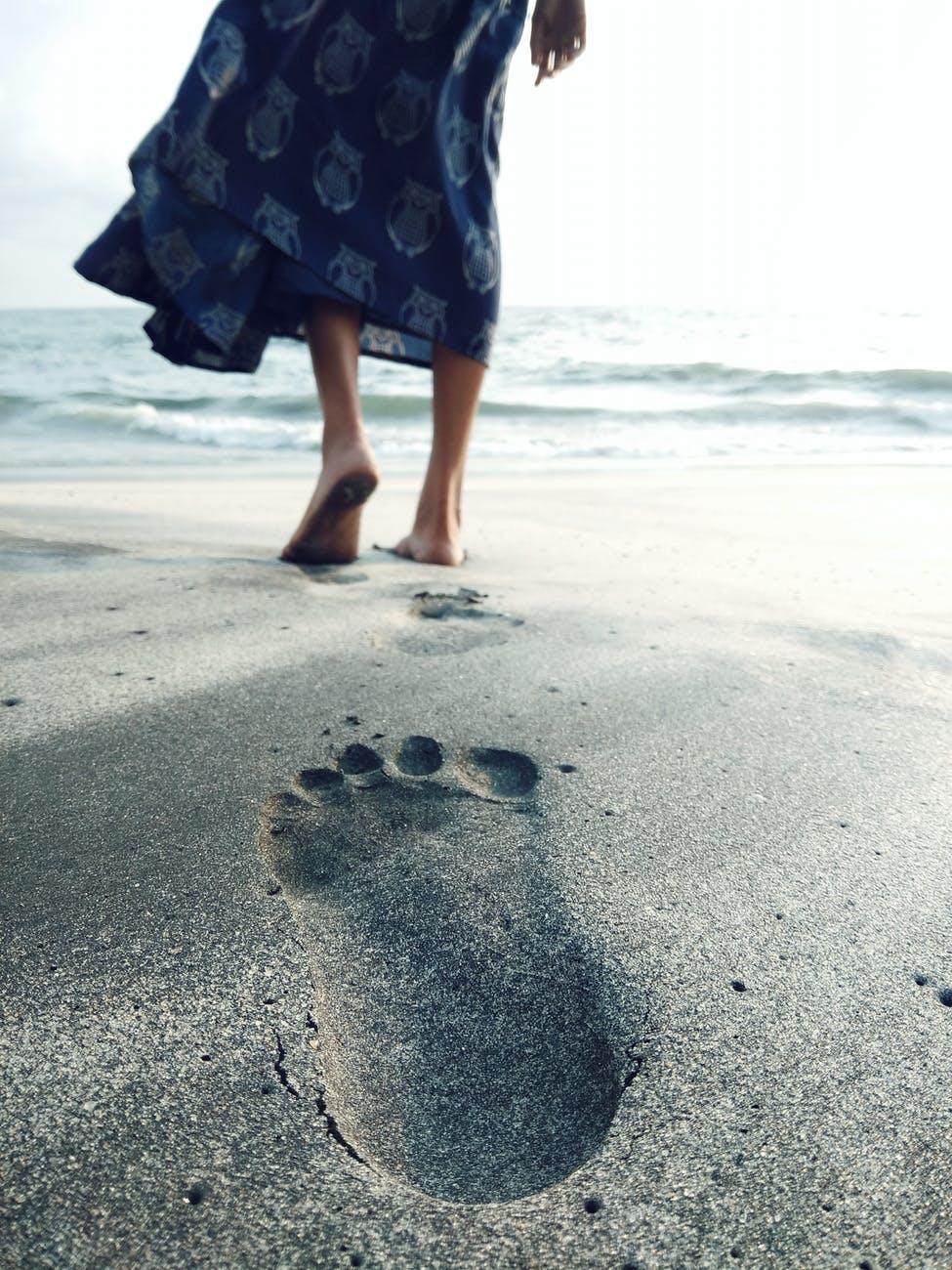 photo of woman walking barefoot on seashore