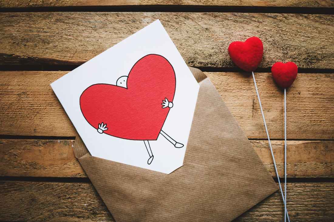 white black and red person carrying heart illustration in brown envelope