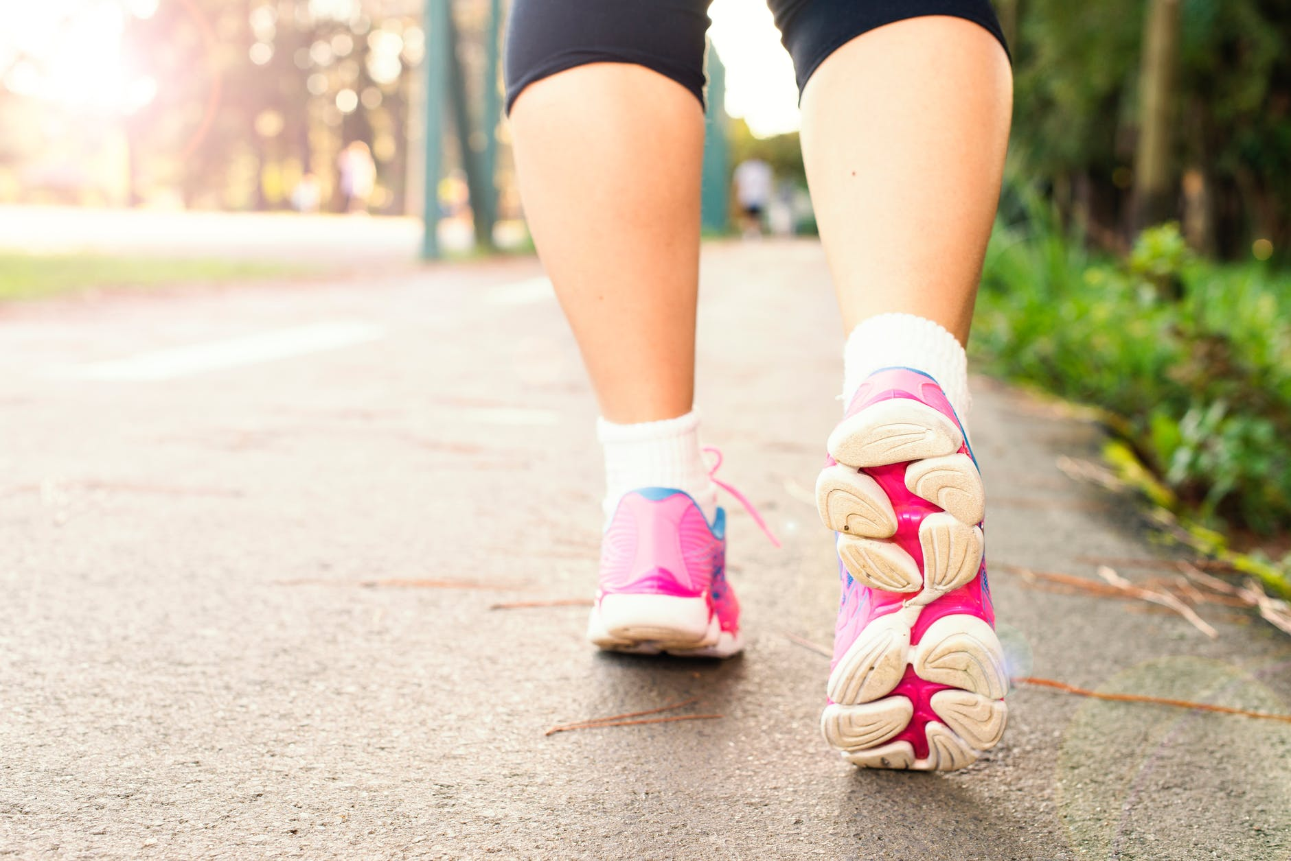 photo of woman wearing pink sports shoes walking