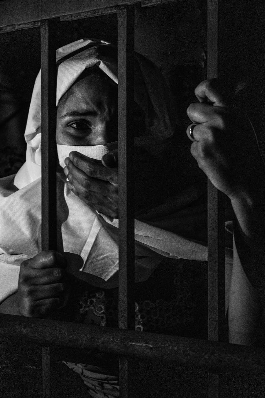 grayscale photography of woman inside jail