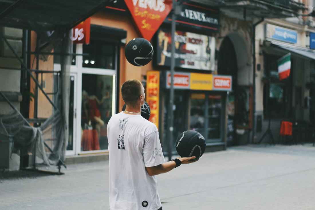 man juggling basketballs near storefront
