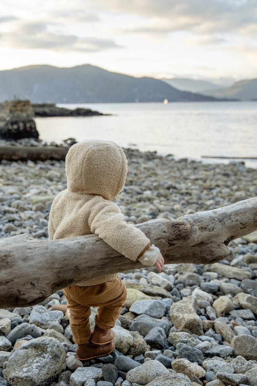 cute little kid leaning on log while resting on rocky coast