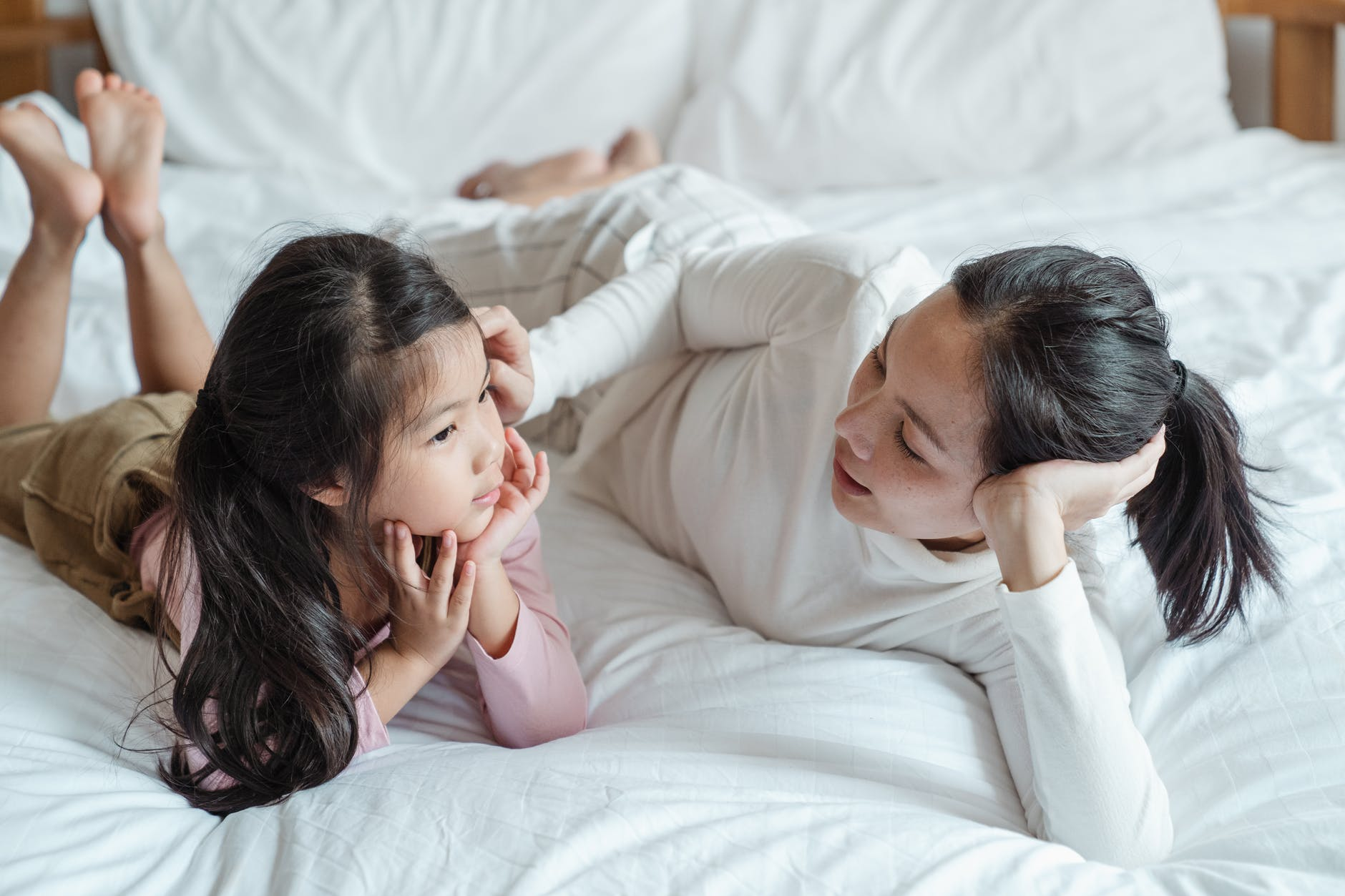 photo of woman and girl talking while lying on bed